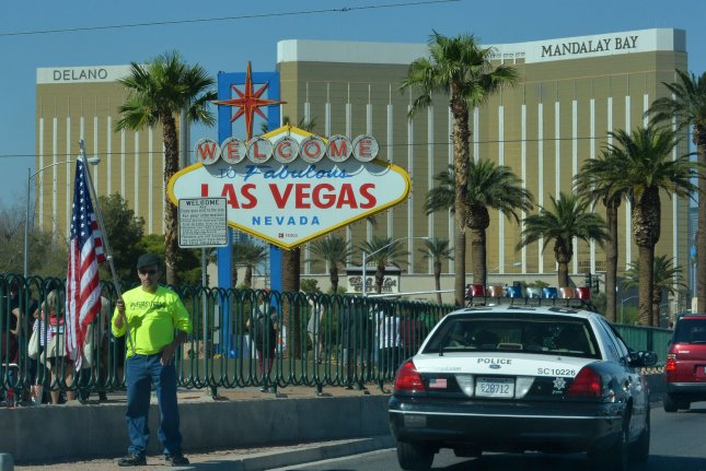 A man greets passing cars with a #Vegasstrong T-shirt and an American flag as they arrive on Las Vegas Boulevard on October 4 near site of the October 1 mass shooting where 58 people were killed and more than 500 injured while attending the three-day Route 91 Harvest country music festival in Las Vegas. On Friday, investigators said they believe the shooter intentionally fired upon fuel tanks at the nearby airport. Photo by Jim Ruymen/UPI