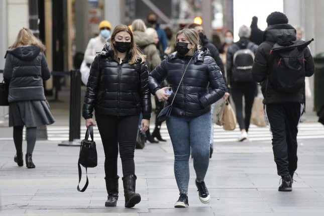 Pedestrians wear face masks to protect from and to prevent the spread of COVID-19 as they walk on Fifth Avenue in New York City on Tuesday, Several European countries have or is considering delaying the second dose of a vaccine meant to stop the virus. Photo by John Angelillo/UPI