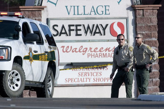 Pima County, Ariz., Sheriff's deputies stand guard at the entranceway to the assassination site one day after a gunman shot and killed six people incuding U.S District Judge John Roll and critically injured U.S Rep. Gabrielle Giffords in Tucson on January 8, 2011. File Photo by Gary C. Caskey
