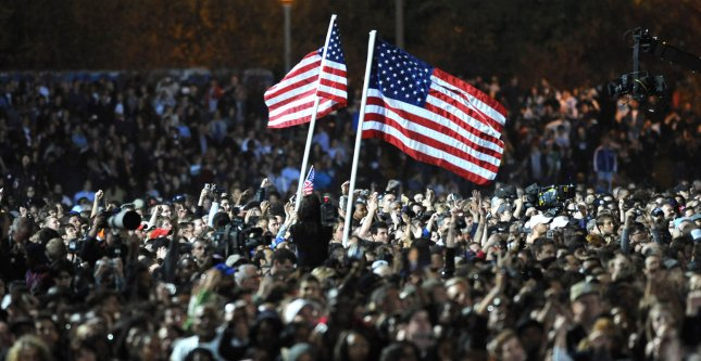 Two American flags rise above a sea of people during an announcement that Democratic presidential candidate Barack Obama was declared the winner in another state by the TV networks at the Obama election night rally in Grant Park in Chicago on November 4, 2008. More than 65,000 people are expected at the rally. (UPI Photo/Pat Benic)