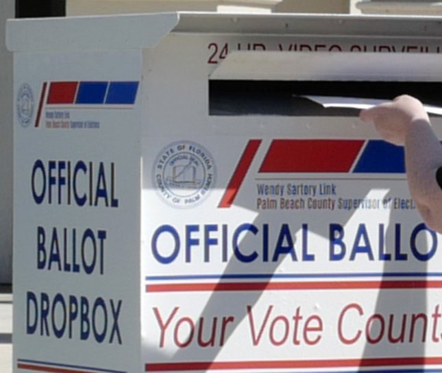 A resident of Palm Beach County places a ballot in the lockbox located at the Supervisor of Elections for Palm Beach County in West Palm Beach, Florida, on Tuesday. Photo by Gary I Rothstein/UPI