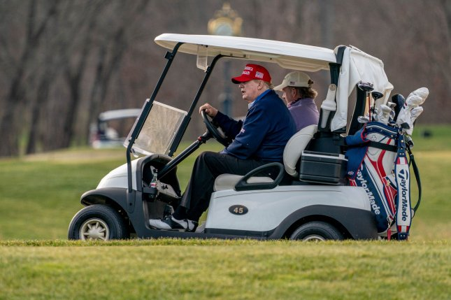 President Donald Trump drives a golf cart as he plays golf Sunday at the Trump National Golf Club in Sterling, Va. Photo by Ken Cedeno/UPI