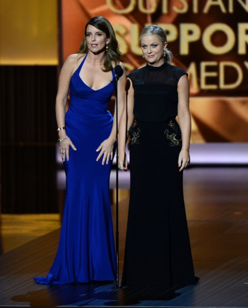 Tina Fey (L) told E! News at Sunday's Emmy Award show she and Amy Poehler (R) are considering serving as co-hosts of the Golden Globe Awards ceremony in Los Angeles for a second consecutive year. Fey and Poehler are pictured onstage last night at the 65th Emmy Awards on September 22, 2013. UPI/Jim Ruymen
