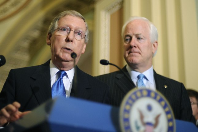 Senate Minority Leader Mitch McConnell (R-KY) speaks alongside Sen. John Cornyn (R-TX) on Capitol Hill. In a surprising move, both voted to end debate on a 'clean' debt-ceiling bill and move it forward for a vote, after a 15-minute huddle with top Republicans on Feb. 12, 2014. (UPI Photo/Kevin Dietsch)