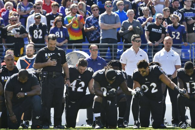 The Baltimore Ravens lock arms and kneel before standing for the National Anthem during an NFL game against the Pittsburgh Steelers on October 1 at M&T Bank Stadium in Baltimore, Md. Photo by David Tulis/UPI