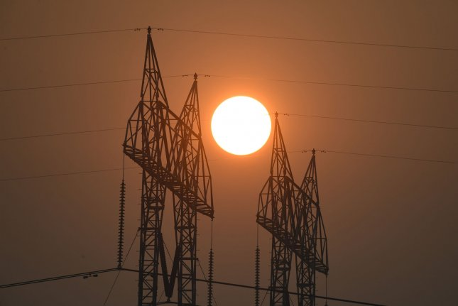 The sun glows through smokey skies behind high tension electricity towers in Butte County, Calif., in 2018. File Photo by Terry Schmitt/UPI