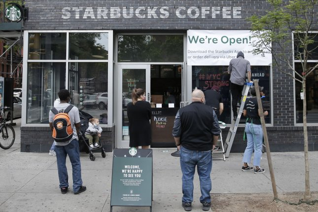 Customers wait as workers hang a sign at a Starbucks Coffee franchise in the East Village neighborhood of Manhattan in New York City on Thursday, May 28, 2020. The COVID-19 pandemic has challenged the U.S. economy. Photo by John Angelillo/UPI