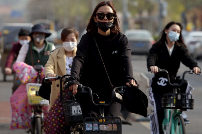 Bicyclists wear protective face masks amid the coronavirus crisis in Beijing on Thursday. China reported 10 new local cases Wednesday and three dozen that were imported. Photo by Stephen Shaver/UPI