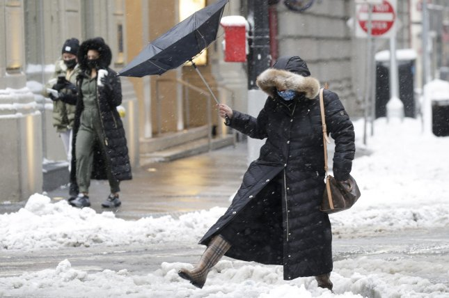 A pedestrian holds a flipped umbrella while she takes a giant step over a wet puddle in New York City on Thursday. Photo by John Angelillo/UPI