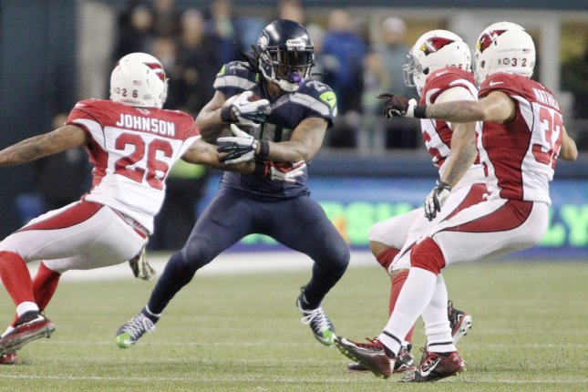 Seattle Seahawks running back Marshawn Lynch (24) can't find running room by Arizona Cardinals Rashad Johnson (26) Lamarr Woodley (56) and Tyrann Mathiew (32) at CenturyLink Field in Seattle, Washington on November 15, 2015. The Cardinals beat the Seahawks 39-32. Photo by Jim Bryant/UPI