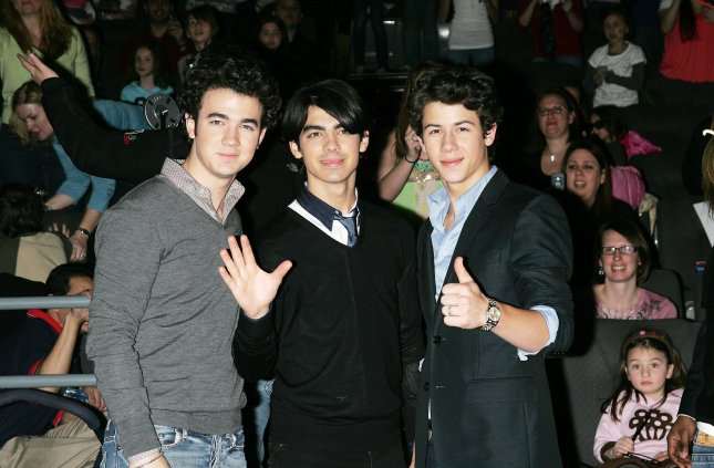 The Jonas Brothers (L-R) Kevin, Joe and Nick surprise fans at the AMC Loews IMAX Theater before a showing of their movie in Nyack, New York on February 28, 2009. (UPI Photo/Laura Cavanaugh)