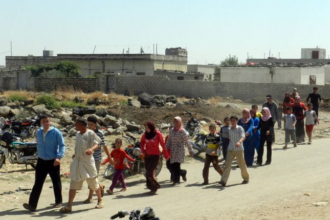 Syrian civilians flee in a vehicle at Houla near Homs, September 9, 2012. UPI