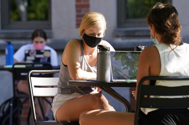 Masked students sit outdoors at a cafe on the Saint Louis University campus in St. Louis, Mo., on Wednesday. Photo by Bill Greenblatt/UPI