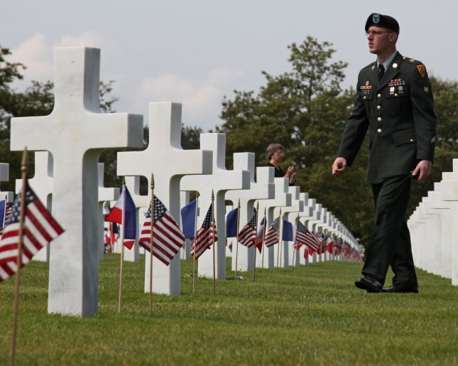 A Soldier Walks Past Rows Of White Crosses At The Normandy American Cemetery In Colleville Sur Mer To Attend Ceremony Commemorating 65th Anniversary