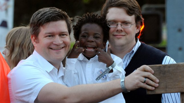 Duncan Ireland (R) and his husband John Ireland hold their son Watson Ireland, 4, as they join gay marriage supporters at a rally in California on May 26, 2009. (UPI Photo/Jim Ruymen). .