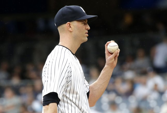 New York Yankees starting pitcher J.A. Happ holds up a baseball in the first inning against the Toronto Blue Jays at Yankee Stadium in New York City on August 19, 2018. Photo by John Angelillo/UPI