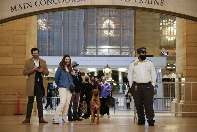 A transit worker stands with people who wait on line to be vaccinated when New York City opens up a pop-up vaccine site in Vanderbilt Hall at Grand Central Terminal. File Photo by John Angelillo/UPI