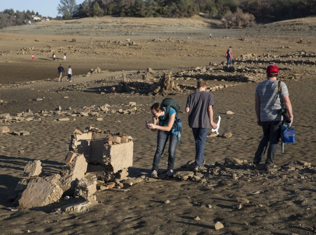 People look over remains of the old Gold Rush settlement of Mormon Island which has resurfaced due to the historic low water levels of Folsom Lake, in Folsom, California, on January 19, 2014. California Governor Jerry Brown declared a state wide drought last Friday. UPI/Ken James