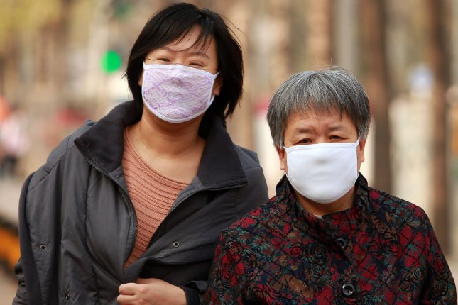 Chinese women wear face masks to protect from the H7N9 virus outbreak that has infected 135 people and killed 44 in China. Researchers have found that the virus is resistant to drugs and continues to retain its disease causing abilities. (File/UPI/Stephen Shaver)