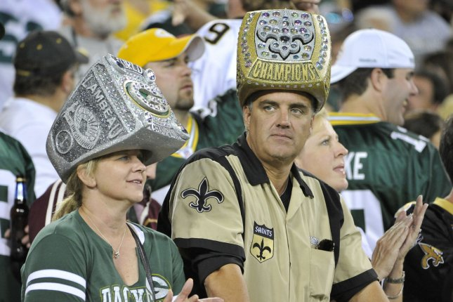A Green Bay Packers fan (L) and a New Orleans Saints fan both wear Super Bowl ring hats during the second quarter of the Saints Packers game at Lambeau Field on September 8, 2011 in Green Bay, Wisconsin. File photo Brian Kersey/UPI