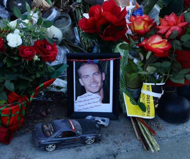Fans gather at a memorial at the site of the car accident in which Paul Walker was killed in Dec. 4, 2013. Walker's daughter, Meadow, reached a wrongful death settlement with Porsche for the crash that killed her father. File Photo by Jim Ruymen/UPI