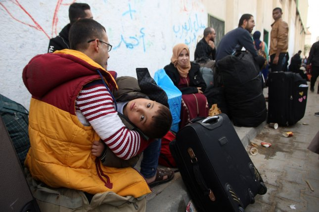 Palestinians wait for travel permits Saturday to cross into Egypt after Hamas ceded the Rafah border crossing to the Palestinian Authority in the southern Gaza Strip. The Gaza-Egypt border is temporarily open for three days. Photo by Ismael Mohamad/UPI
