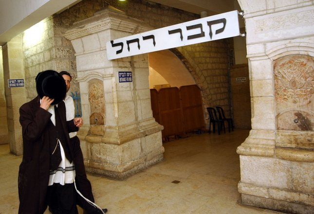 An Ultra-Orthodox Jew covers his face with his hat in Rachel's Tomb in the Biblical city of Bethlehem, September 15, 2004. (UPI Photo/Debbie Hill)