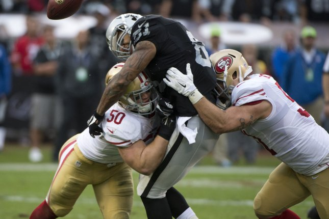 Oakland Raiders TE Mychal Rivera is sandwiched on a QB Derek Carr by San Francisco 49ers Chris Borland (50) and Ray McDonald in the third quarter at O.co Coliseum in Oakland, California on December 7, 2014. The Raiders defeated the 49ers 24-13. UPI/Terry Schmitt