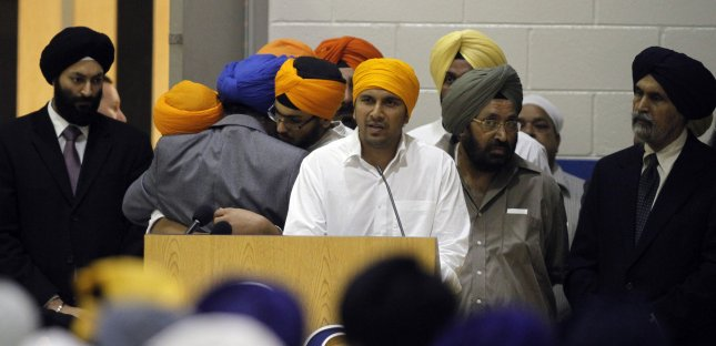 Amardeep Singh Kaleka (L), son of of assassinated Sikh Temple President Satwant Kaleka, speaks with other Sikh members hugging during a visitation and memorial service for six members of the Sikh Temple at Oak Creek High School in Oak Creek, Wisconsin August 10, 2012. Wade Michael Page, a member of a racist neo-Nazi group, has been identified as the gunman who killed six people, and then himself, during Sunday services at the Sikh Temple August 5. UPI /Allen Fredrickson