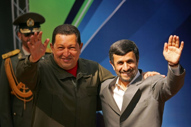 Iran's President Mahmoud Ahmadinejad (R) and Venezuela's President Hugo Chavez wave for media during a welcoming ceremony for Chavez in Tehran, Iran on April 2, 2009. UPI/Mohammad Kheirkhah