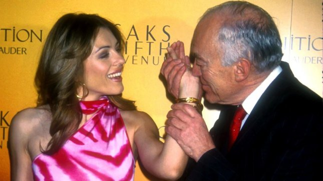 Estee Lauder Chairman Leonord Lauder smells perfume on the wrist of Estee Lauder spokesperson Elizabeth Hurley. Some cities are trying to control perfume use, which can aggravate symptoms for allergy sufferers. UPI