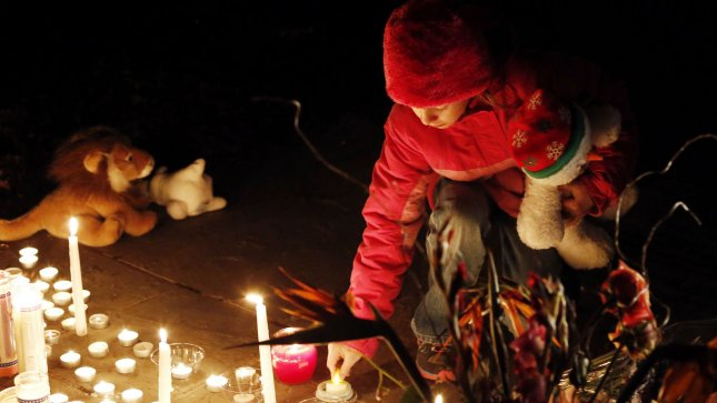 A child lights a candle at a memorial filled with flowers, stuffed toys and candles outside of Saint Rose of Lima Church near Sandy Hook Elementary School in Newtown, Connecticut following a shooting the day before at the school that left 27 people dead including 18 children on December 15, 2012. A gunman opened fire inside Sandy Hook Elementary School early Friday morning where his mother worked. The suspect 20-year-old Adam Lanza, reportedly killed himself following the shooting rampage inside the school. UPI/John Angelillo