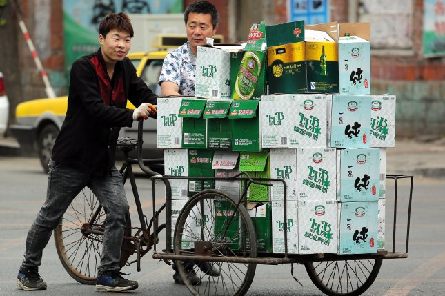 Chinese men push a tricycle stacked with cases of beer to a waiting van in Dandong, China's largest border city with North Korea. Photo by Stephen Shaver/UPI