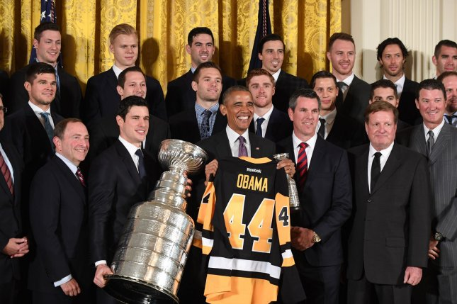 U.S. President Barack Obama holds his jersey as Pittsburgh Penguins Sidney Crosby holds the Stanley Cup during event honoring the NHL 2016 Stanley Cup Champions Pittsburgh Penguins in the East Room of the White House in Washington, DC on October 6, 2016. From left, NHL Commissioner Gary Bettman, Crosby, Obama, coach Mike Sullivan, owner Ronald Burkle, and owner Mario Lemieux. Photo by Pat Benic/UPI