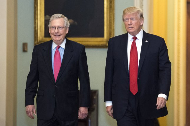 President Donald Trump (R) walks with Senate Republican leader Mitch McConnell as Trump arrives for a Republican Senate luncheon meeting at the U.S. Capitol on Tuesday. Photo by Kevin Dietsch/UPI