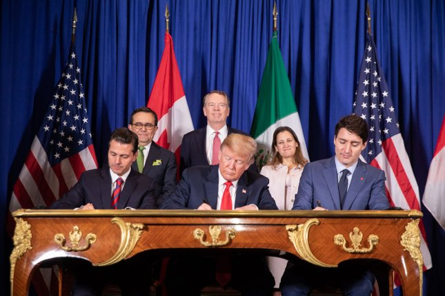 President Donald Trump, joined by Mexican President Enrique Pena Nieto and Canadian Prime Minister Justin Trudeau, signs the North American Free Trade Agreement replacement last year in Argentina. The legislation has hit a snag in Congress. File Photo by Shealah Craighead/UPI