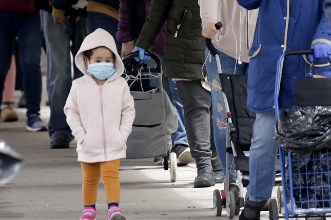 A child wears a protective face mask while adults wait on line at a food distribution for neighborhood people affected by the COVID-19 pandemic in New York City on Monday. The CDC has confirmed the link between a rare, potentially deadly syndrome in children resembling Kawasaki's Disease.with COVID-19. Photo by John Angelillo/UPI