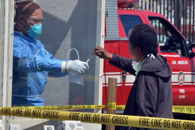 A woman administers a COVID-19 self-testing kit at a L.A. Fire Department pop-up testing station, where workers in hazmat suits handed out testing swabs to the homeless from behind a protective window on April 21. Photo by Jim Ruymen/UPI