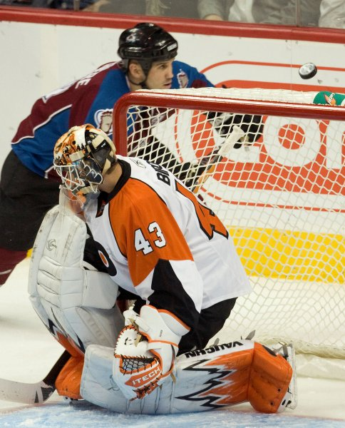 Colorado Avalanche right wing Ian Laperriere (top) chases a rebound behind Philadelphia Flyers goalie Martin Biron at the Pepsi Center in Denver on October 16, 2008. Colorado beat Philadelphia 5-2. (UPI Photo/ Gary C. Caskey)