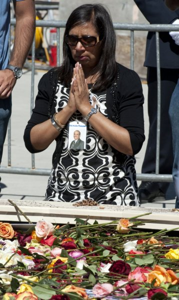 A woman prays by the reflecting pool at Ground Zero during a ceremony in memory of victims of the 9/11 terrorist attacks September 11, 2010 in New York City. Thousands gathered to pay solemn homage on the ninth anniversary of the terrorist attacks that killed nearly 3,000 people on September 11, 2001. UPI/Don Emmert/Pool