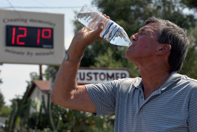 John Rinehart takes a drink of water near a thermometer as the temperature hits 121 degrees in Phoenix on Tuesday. A heat wave has gripped the Southwest through the weekend. Photo by Art Foxall/UPI