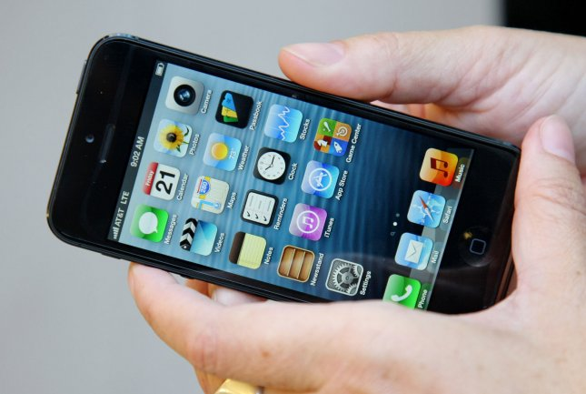 A customer holds a new iPhone 5 at the Apple Flagship Store on Fifth Avenue as the device goes on sale for the first time on Sept. 21 in New York City. The new version of Apple's smartphone features a slimmer design, larger screen and a faster web browsing speed. UPI /Monika Graff