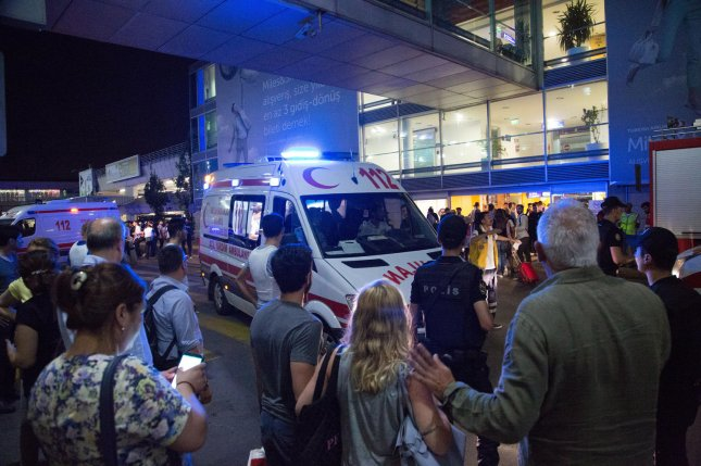 Turks gathers while forensic police work the explosion site at Ataturk airport after gunfire and explosions hit Turkey's biggest airport, killing 44 on Tuesday. Turkish police have arrested 41 people in connection with the attack. Photo by Laurance Cameron/UPI