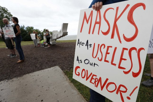 Activists hold signs during a protest against Ohio's mandatory order requiring face coverings during the coronavirus pandemic, at Edgewater Park in Cleveland, Ohio, on July 11. Similar orders have been enacted nationwide, but some areas are challenging the mandates in court. Photo by Aaron Josefczyk/UPI
