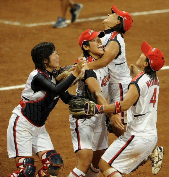 Japanese players surround pitcher Yukiko Ueno (C) as they celebrate the last out, as Japan wins the gold medal against the USA women's team, 3-1, at Fengtai Softball Field, August 21, 2008, at the Summer Olympics in Beijing. The USA team had beaten Japan in an earlier match. Australia won the bronze. (UPI Photo/Mike Theiler)