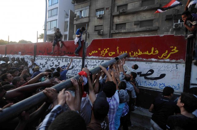 Egyptian demonstrators try to demolish a wall recently built outside the Israeli embassy in Cairo to protect the building . Around 1,000 people had gathered outside the building housing the mission and attacked the wall with hammers and a large metal bar, while military police nearby did nothing to stop them, in Cairo, in Egypt on September 9, 2011. UPI/ Mohamad Hosam