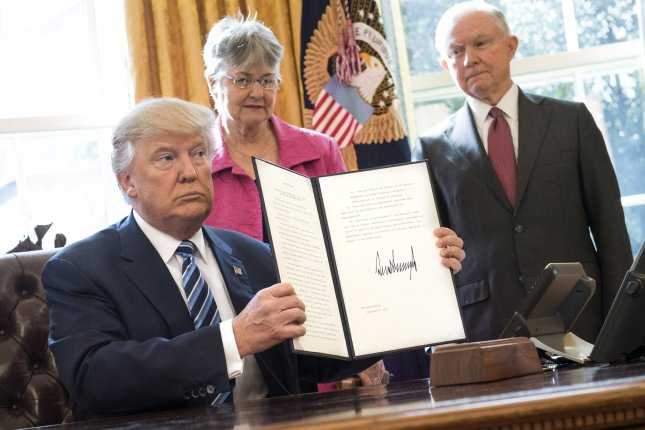 President Donald Trump holds up one in a series of three executive orders that Trump said will restore safety in America after swearing-in Attorney General Jeff Sessions (R) in the Oval Office at the White House on Thursday. Sessions' wife, Mary, also attended. Photo by Kevin Dietsch/UPI