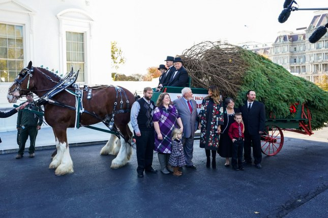 First lady Melania Trump greets Larry Snyder and his family as the official White House Christmas is delivered at the White House. Photo by Kevin Dietsch/UPI