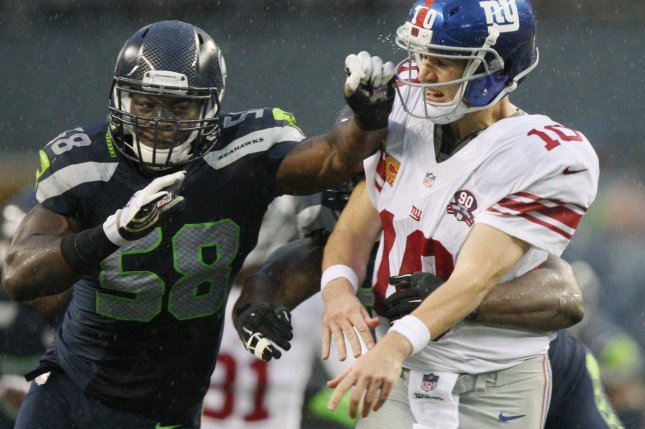 New York Giants quarterback Eli Manning (10) takes a hit from former Seattle Seahawks linebacker Kevin Pierre-Louis (58) and linebacker K.J. Wright (50) on November 9, 2014 at CenturyLink Field in Seattle, Washington. File photo by Jim Bryant/UPI