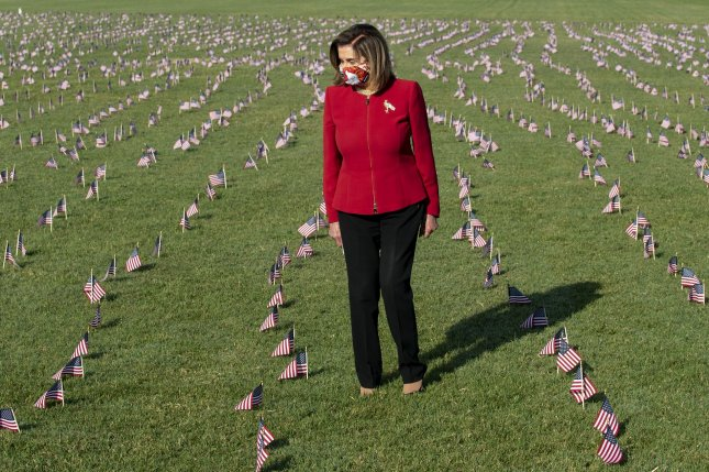 House Speaker Nancy Pelosi walks amongst the 200,000 American flags during an event Tuesday commemorating the 200,000 Americans that have lost their lives due to the COVID-19 pandemic, on the National Mall in Washington, D.C. Photo by Pat Benic/UPI